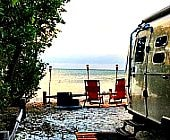 Airstream trailer by ocean with red chairs
